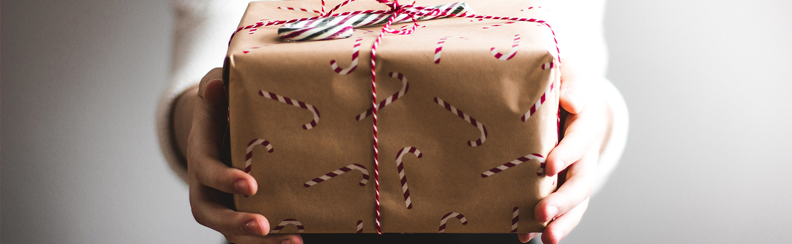 person holding out wrapped christmas gift