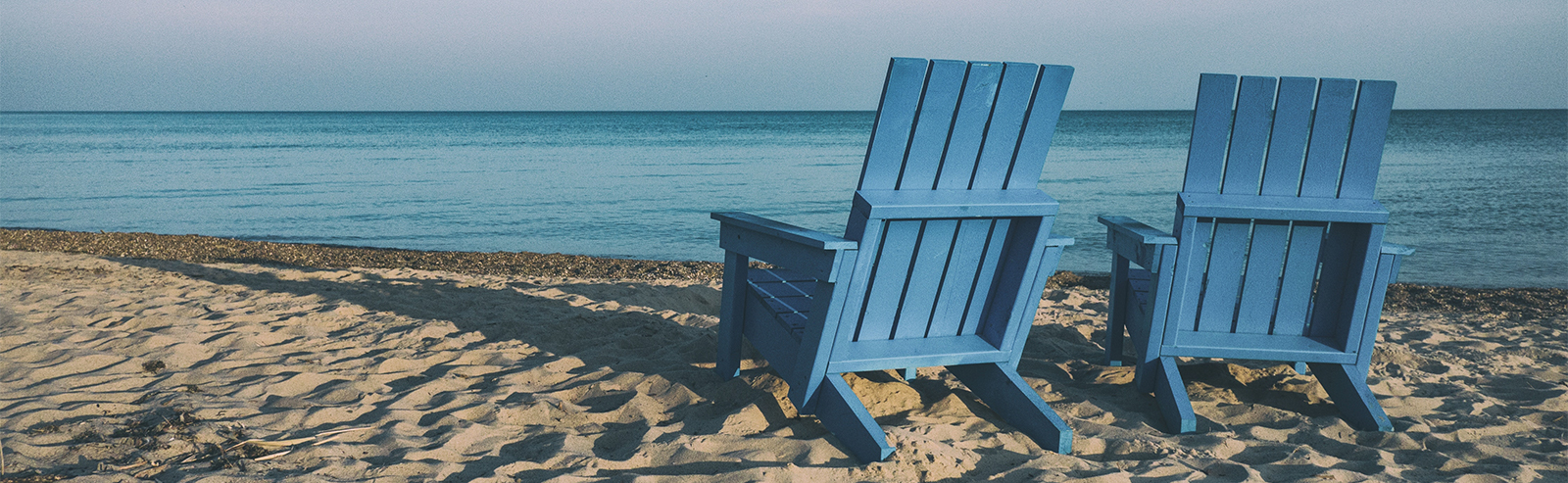 blue chairs sitting on a beach in front of the ocean