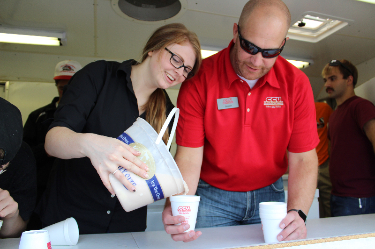 two employees pouring milkshakes
