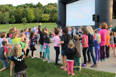 group of kids dancing in front of outdoor movie screen
