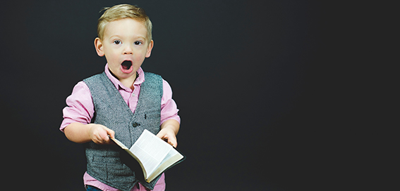 a kid with a surprised look holding a book