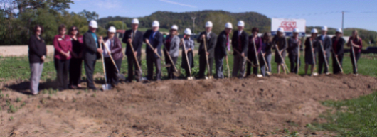 people holding shovels while breaking ground on new building